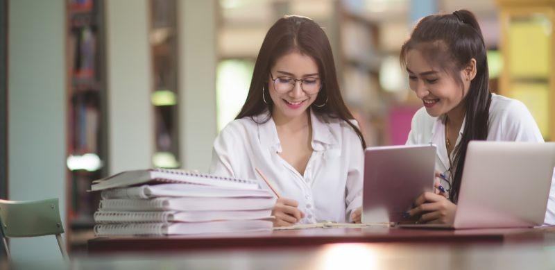 Fotografia de duas mulheres estudando com cadernos e dispositivos tecnológicos.