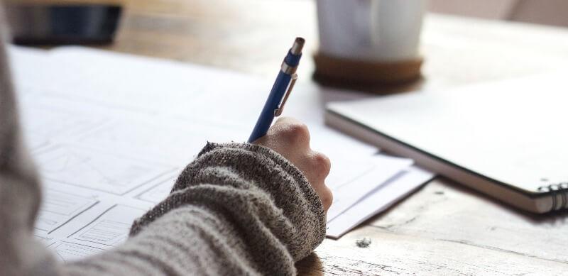 A importância da redação na escola: fotografia de uma pessoa escrevendo em uma folha.