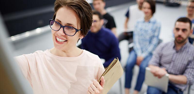 O que é gestão escolar: fotografia de uma mulher sorrindo escrevendo em algo. Atrás, estão outras pessoas observando.