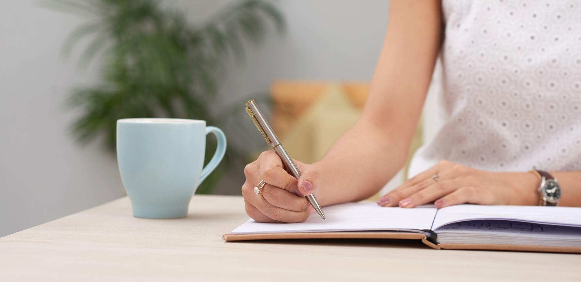 plano de gestão escolar: imagem de uma mulher escrevendo em uma folha