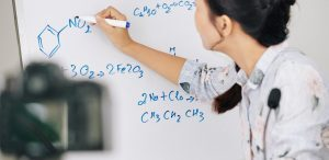 como fazer uma boa videoaula: imagem de uma mulher escrevendo fórmulas químicas no quadro