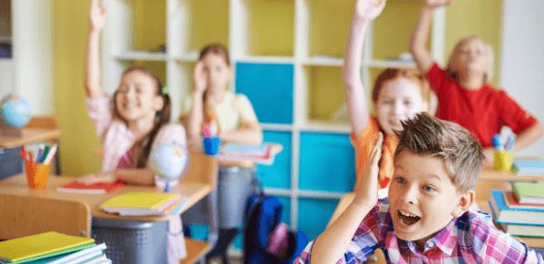 Metodologias ativas segundo a bncc: imagem de várias estudantes com a mão levantada para participar da aula.