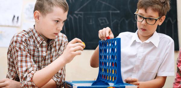 Gamificação na educação: imagem de dois alunos concentrados em um jogo em sala de aula.