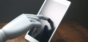 Inteligência Artificial na educação: imagem de uma mão robótica tocando um tablet.
