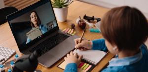 O que quer dizer ensino híbrido: imagem de uma estudante em frente a um notebook, fazendo anotações da sua aula online.