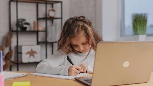 O papel da tecnologia na educação: imagem de uma menina estudando em casa com o computador